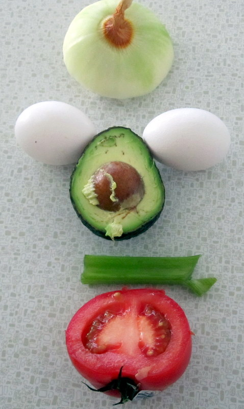 key ingredients for spicy scrambled eggs with onion, garlic, celery, tomato and avocado