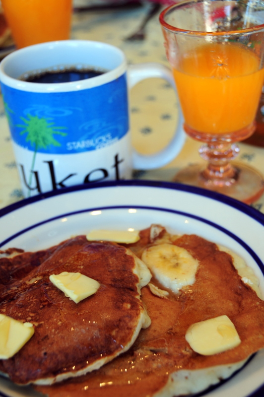 enjoying buttermilk pancakes with caramelized banana and walnuts with black coffee, freshly squeezed orange juice, maple syrup and lots of butter