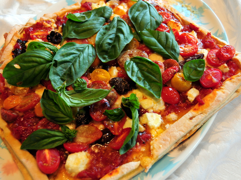 rustic pizza with feta, heirloom cherry tomatoes, kalamata and marinara