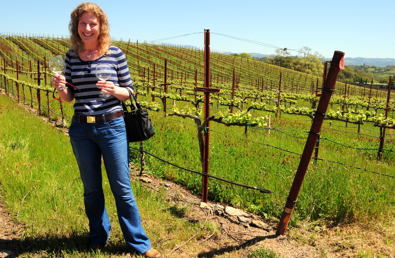 Jasmine standing at the vineyard's edge with two empty Williams Selyem wine glasses